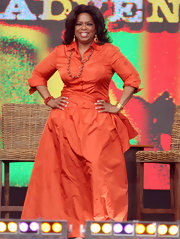 Oprah looks divine in a red orange floor length gown with a button up bodice.