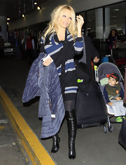 Pamela Anderson stepped out in black over the knee boots, which she paired with a striped sweater dress and opaque tights.