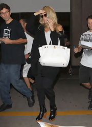 Pamela Anderson wore a big white Hermes Birkin with her casual airport outfit.