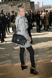Estelle Lefebure stopped to pose for the photog's at Paris Fashion Week. She rocked a grey trench coat, black wedge heels and a cool patent leather tote.