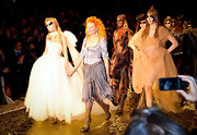 Vivienne Westwood sported an enchanting ensemble at her fashion show, consisting of a corset top, a flirty skirt, and glittery gold mid-calf boots.