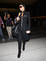 Paris traveled in style through LAX in a black coat paired with black suede over-the-knee boots.