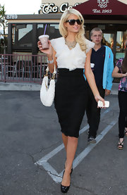 While making a papparazzi frenzy out of gettting a quick coffee. Paris Hilton showed off her leather shoulder bag, which she paired with a pencil skirt and a ruffled blouse.