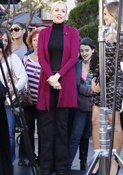 Penelope Ann Miller punctuated her all black attire with a long berry cardigan.