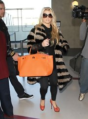 Jessica Simpson traveled through LAX in a black and tan fur coat. She topped off the look with an orange leather tote and platform pumps.