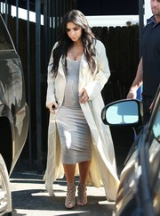 Kim Kardashian wore a light gray maternity dress under an ankle-length coat for a visit to a Los Angeles studio.