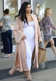 A pregnant Kim Kardashian traded in her towering stilettos for a pair of flat Alaia sandals for a day of shopping.