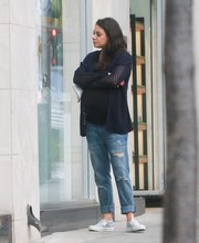 Mila Kunis teamed a navy open-weave cardigan with ripped jeans for a day out in Beverly Hills.