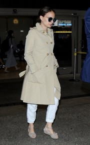 Natalie Portman caught a flight wearing low wedge sandals and a classic trenchcoat.