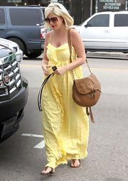 Tori Spelling complemented her sunny maxi dress with a bohemian tan leather satchel.