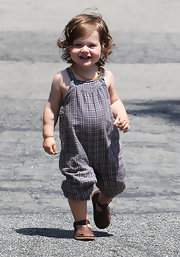 A smiling Skyler Berman looks delightful in his adorable plaid print romper & summery brown sandals.