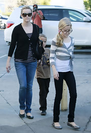 Ava's black skinny pants go perfectly with her wrap sweater and ballet flats.