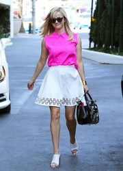 Reese Witherspoon looked oh-so-cute in her laser-cut white Monica Rose for Lovers + Friends mini skirt.