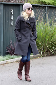 Reese bundles up in a wool coat and knee high boots.