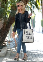 Reese Witherspoon had both hands full, toting a blue and white striped duffle along with her shopper bag.