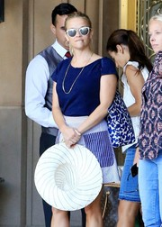 Reese Witherspoon geared up for a summer's day with a white straw hat by Draper James.