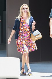 Reese Witherspoon paired her cute dress with a navy cardigan.