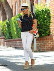 Reese Witherspoon donned a cute pin-dot blouse from her own label Draper James for a day at the office.