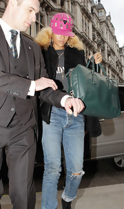 Rihanna embraced color in London with a bright pink cap and teal leather tote.