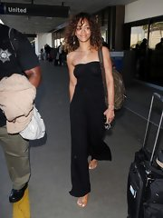 Rihanna traveled in cognac flat sandals.