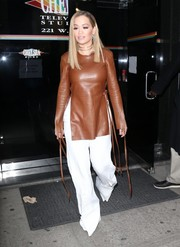 Rita Ora teamed her top with white wide-leg pants.
