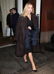 Rita Ora headed out in New York City wearing an oversized brown wool coat over a ruffle-accented dress.