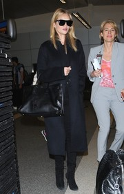 Rosie Huntington-Whiteley arrived on a flight at LAX wearing a midnight-blue wool coat by Acne Studios.