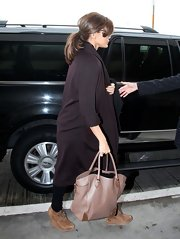 Eva Mendes caught a flight at the LAX airport wearing a pair of brown suede wedge heels with thin laces.