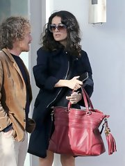 Salma Hayek added a pop of color to her look while out with her family when she carried this red oversized tote bag.