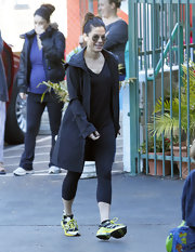 Sandra Bullock beat the chill in a simple black rain coat and workout clothes.