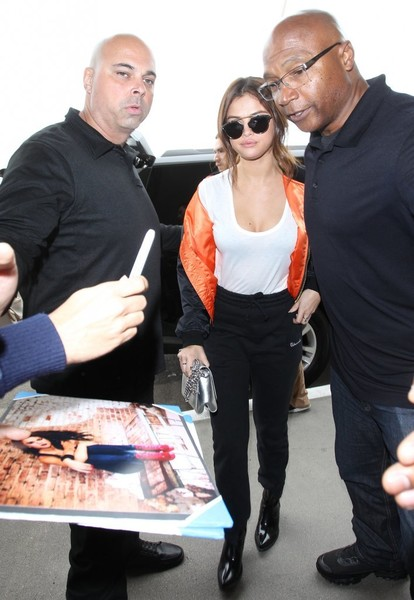 Selena Gomez flew out of LAX wearing a low-cut white T-shirt.