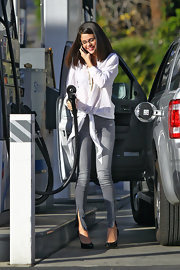 Selena Gomez updated her retro tie blouse with zip-ankle jeans.