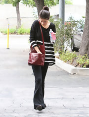 Selena Gomez accessorized her casual outfit with a red cross body bag for a pop of color.