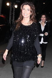 Shania Twain layered a black sequin top over a long sleeve knit tunic, for a dressed-up cozy look.