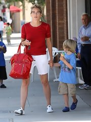 Sharon Stone paired her red shirt with a matching patent leather tote bag.