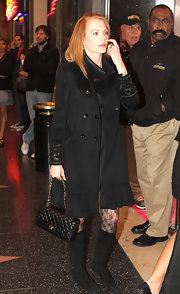 Marg looked timeless in flat black suede boots. She wore them over floral lace tights for a feminine touch.