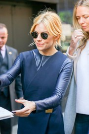 Sienna Miller looked stylish in her Ray-Ban shades while signing for fans.