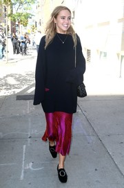 Suki Waterhouse chose a fuchsia satin skirt to pair with her sweater.