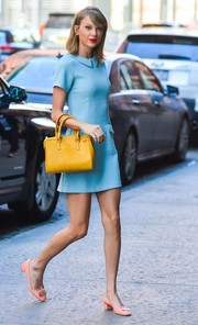 Taylor Swift really played with colors, teaming her blue dress and peach shoes with a yellow Serapian leather tote.