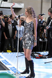 Taylor Swift gave her glittering mini dress a country twist with leather knee-high boots, the perfect footwear for dancing around on stage.