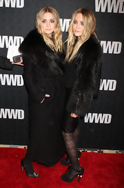 Ashley wears a floor length black wool coat with a large fur collar to match her sister's ensemble.