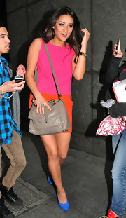 Shay Mitchell toned down her vibrant color-block dress with a taupe leather satchel.