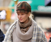 Uma wards off the chill in a plaid wool newsboy cap.