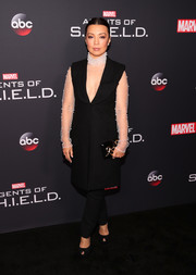 A black hard-case clutch with gold snake detailing finished off Ming-Na Wen's ensemble.