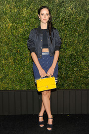 Kaya Scodelario contrasted her all-blue outfit with a canary-yellow purse by Chanel.