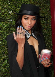 Kat Graham accessorized her black outfit with a metallic silver clutch for a bit of shimmer during the John Varvatos Stuart House Benefit.