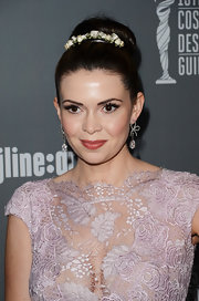 Carly Steel kept her look soft and feminine with a lace gown and and elegant bun topped with a floral headband.