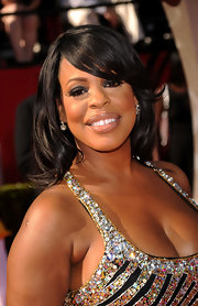 Niecy's hair looks effortlessly styled in soft waves with her bangs swept to the side over her face.