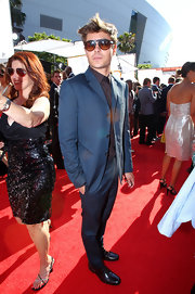 Zac Efron showed off his navy blue suit which he paired with brown shades.