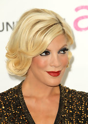 Tori Spelling spiced up her red carpet look with deep red lipstick and a sultry smoky eye.